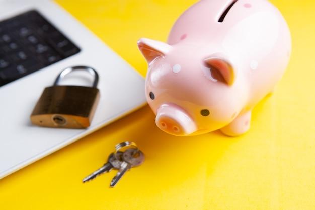 Sparschwein mit einem computersicherheitssystem auf einem laptop.