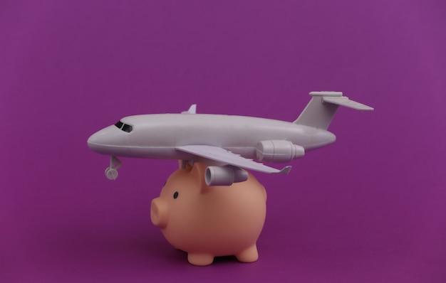 Sparschwein mit einem flugzeug auf einem purpur.