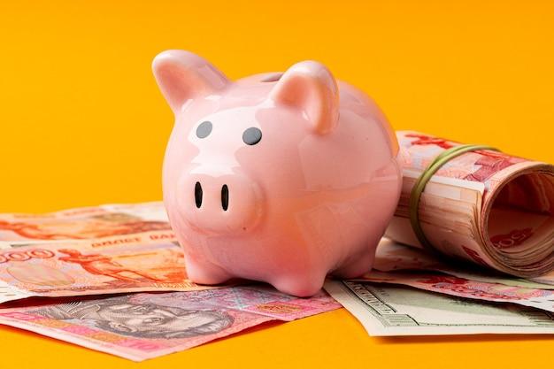 Sparschwein mit geld russische rubel, amerikanische dollar und ukrainische griwna. einsparungskonzept