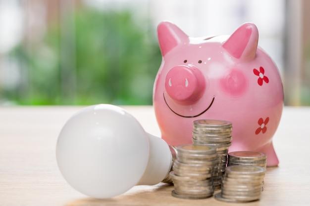 Sparschwein mit glühlampe- und stapelmünzen auf hölzernem schreibtisch - sparen sie energiekonzept.
