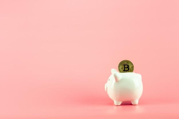 Sparschwein mit goldenem bitcoin auf rosa