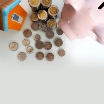 Sparschwein mit kleinem haus und münze auf weißem hintergrund