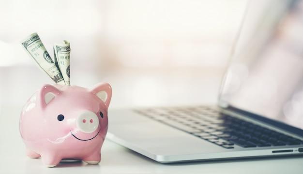 Sparschwein mit laptop auf dem schreibtisch