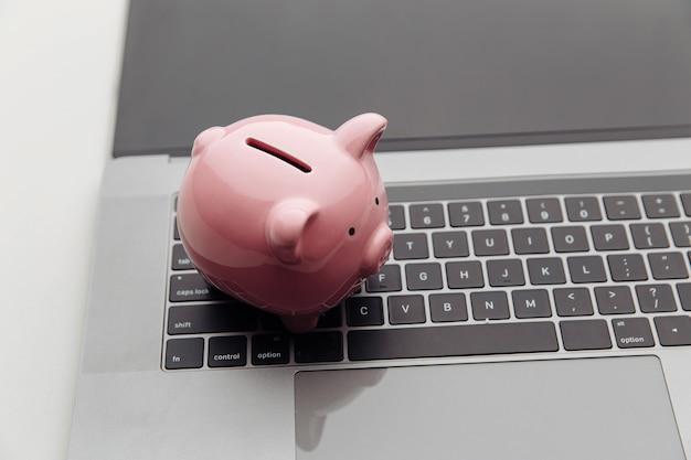 Sparschwein mit laptop auf einem weißen schreibtisch.