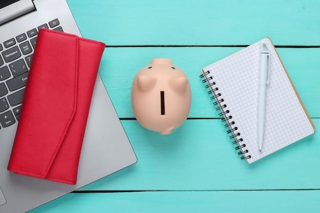 Sparschwein mit laptop, brieftasche, notizbuch auf blauer holzoberfläche. verdienen sie geld online oder im internet geschäftskonzepte. draufsicht. flach liegen