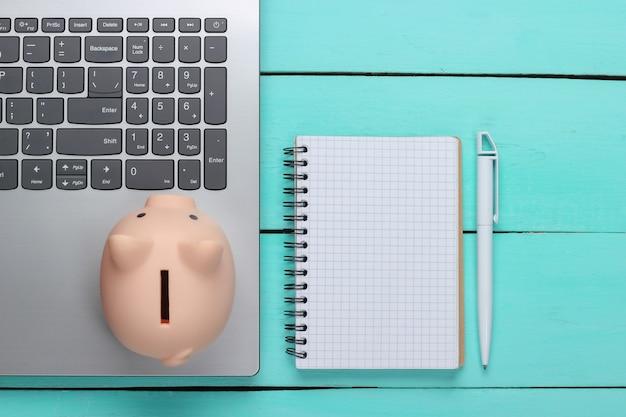Sparschwein mit laptop, notizbuch auf blauer holzoberfläche. verdienen sie geld online oder im internet geschäftskonzepte. draufsicht. flach liegen