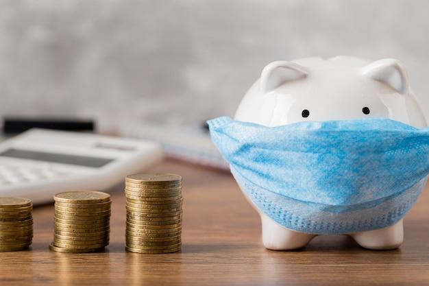 Sparschwein mit medizinischer maske und münzen