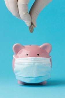 Sparschwein mit medizinischer maske