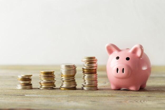 Sparschwein mit münze auf altem holztisch