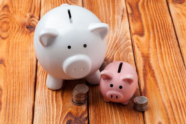 Sparschwein mit münze auf holztisch
