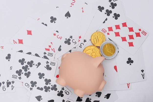 Sparschwein mit münzen auf spielkarten. alles steht auf dem spiel, gewinne