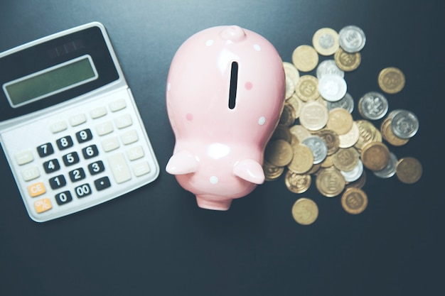Sparschwein mit münzen und taschenrechner auf dunklem tisch