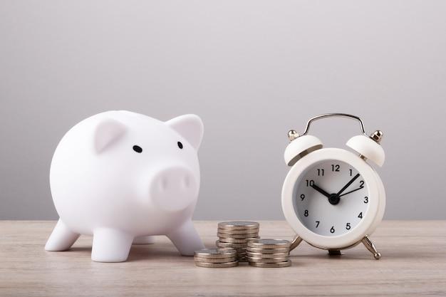 Sparschwein mit münzen und uhr