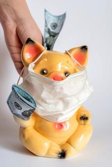 Sparschwein mit schutzmaske gegen coronirus-virus. die hand des menschen bringt dort dollars. selektiver fokus.