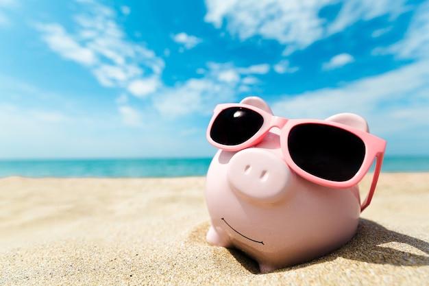Sparschwein mit sonnenbrille am strand entspannen