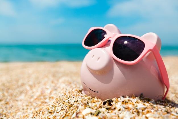 Sparschwein mit sonnenbrille am strand entspannen Premium Fotos