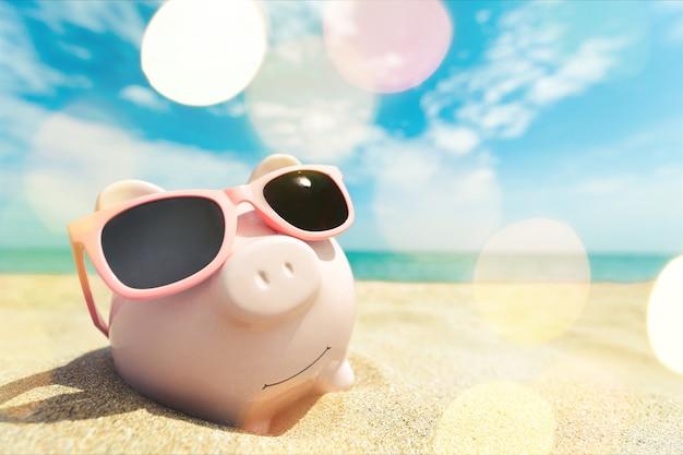 Sparschwein mit sonnenbrille am strandsand