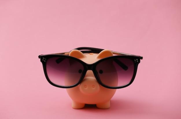 Sparschwein mit sonnenbrille auf einem rosa