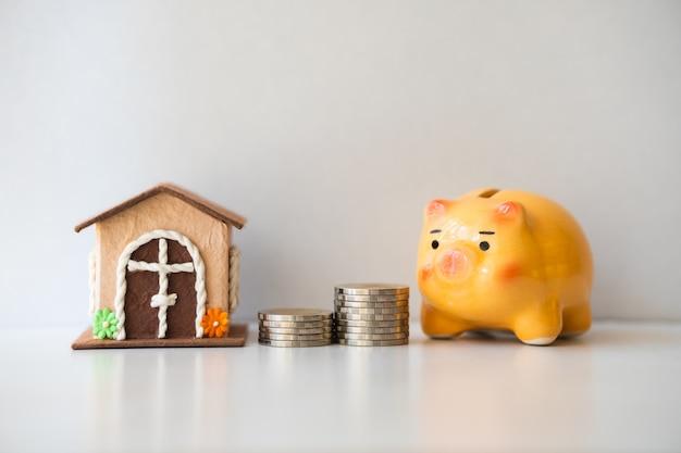 Sparschwein mit stapelmünzen und minihaus unter verwendung als geldeinsparung, geschäfts- und eigentumskonzept