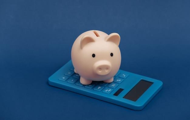 Sparschwein mit taschenrechner auf klassischem blauem hintergrund