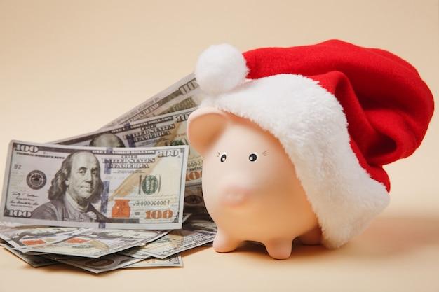 Sparschwein mit weihnachtsmütze bündel von dollar-banknoten bargeld auf beigem hintergrund isoliert. geldakkumulationsinvestitionen, bankdienstleistungen, vermögenskonzept. kopieren sie platzwerbungsmodell.