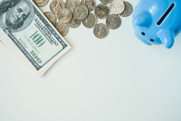 Sparschwein, münzen und stapel dollarscheine