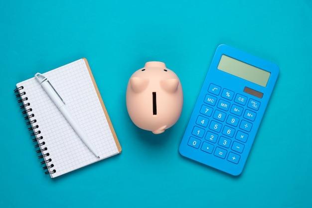 Sparschwein, notizbuch und taschenrechner auf blau