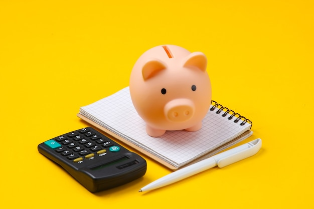Sparschwein, notizbuch und taschenrechner auf gelb