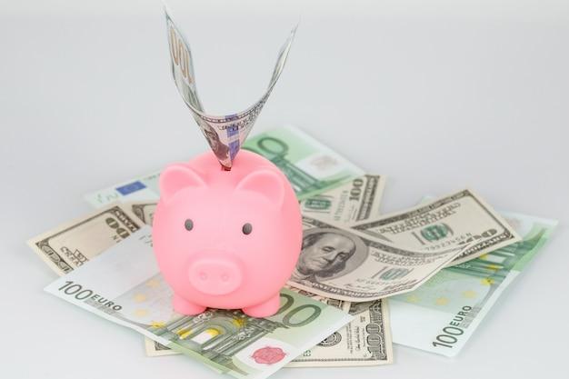 Sparschwein-sparbüchse im stapel von dollar- und euro-banknoten