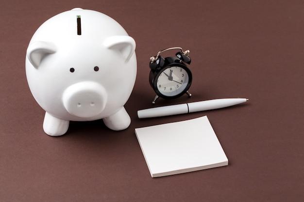 Sparschwein sparen münzen- und wecker-, zeit- und geldkonzept.