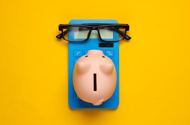 Sparschwein und blauer taschenrechner, gläser auf gelb