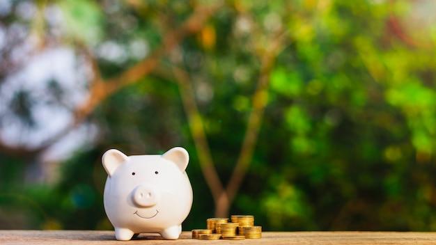 Sparschwein und ein goldener münzenstapel auf altem holztisch.