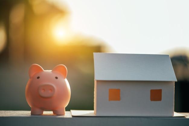 Sparschwein und ein hausmodell, konzept geld sparen für haus und immobilien.