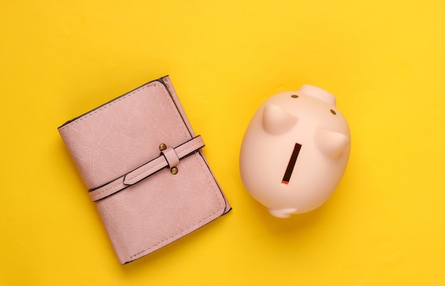 Sparschwein und geldbörse auf gelb.