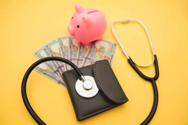 Sparschwein und geldbörse mit stethoskop isoliert auf gelb.