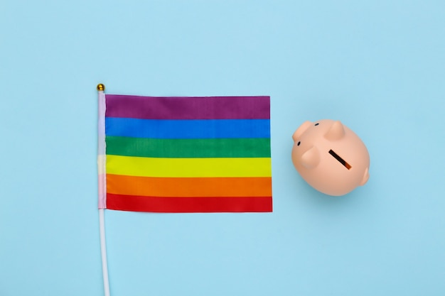 Sparschwein und lgbt-regenbogenflagge auf blauem hintergrund. schwulenparade, freiheit, toleranz