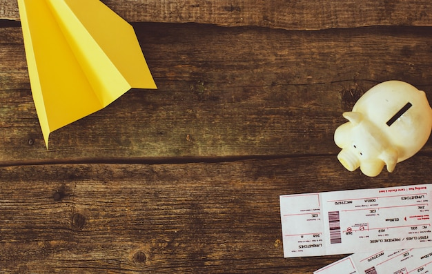 Sparschwein und papierflugzeug auf hölzernem hintergrund