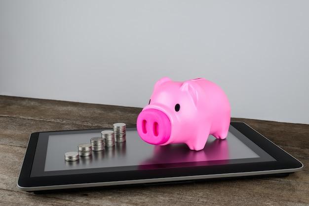 Sparschwein und reihe des münzengeldes auf tablette