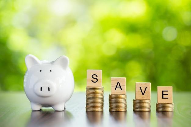 Sparschwein und sparen sie wort auf geldmünze wie stapel wachsendes geschäft mit grünem hintergrund. sparen