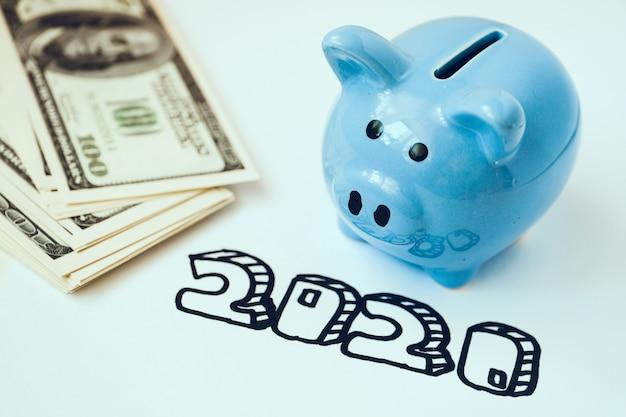 Sparschwein und stapel von hundert dollarscheinen mit aufschrift mit 2020 markierungen