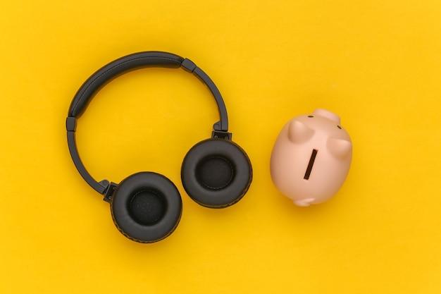 Sparschwein und stereokopfhörer auf braunem beige hintergrund. ansicht von oben