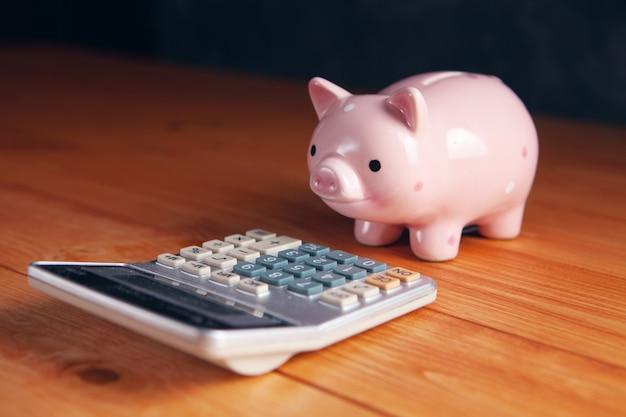 Sparschwein vor dem taschenrechner auf dem tisch
