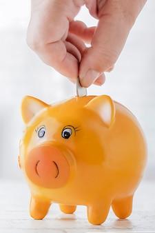 Sparschwein womans hand legt münzen in ein sparschwein