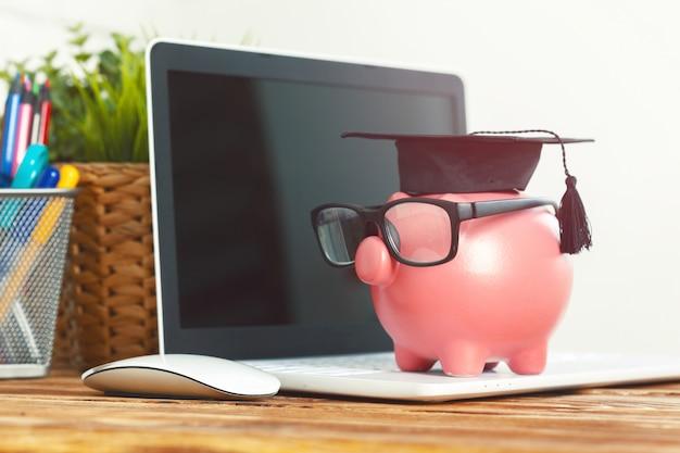 Sparschweinkasten mit laptop auf holztisch