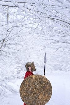 Spartanischer krieger steht im verschneiten wald