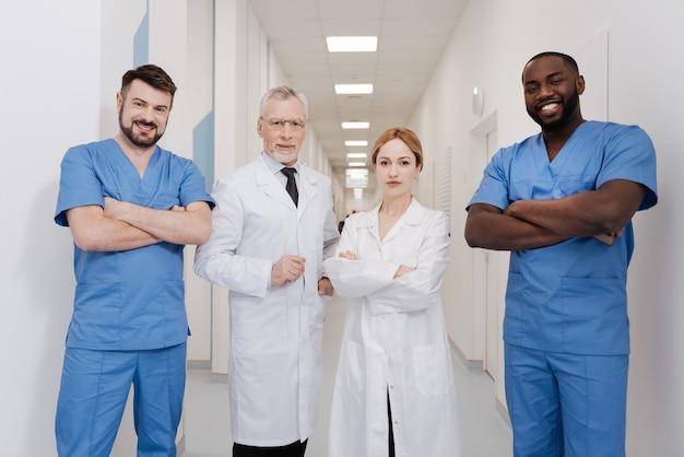 Spaß an der zusammenarbeit. herrliche freudige angenehme ärzte, die in der klinik arbeiten und nahe beieinander stehen und gleichzeitig freude ausdrücken