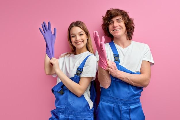 Spaß beim gemeinsamen putzen. glücklicher mann und frau im overall, die gummihandschuhe tragen, die für die reinigung vorbereiten
