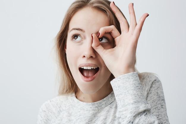 Spaß, freude und glück. bild einer fröhlichen glücklichen jungen frau mit langen blonden haaren mit geöffnetem mund, die mit der hand eine gute geste macht, sich über einen guten tag freut und zeigt, wie großartig sie ist