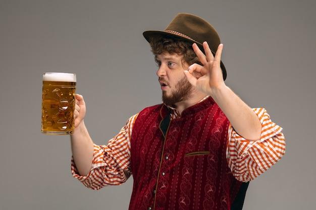 Spaß. glücklicher mann in traditioneller österreichischer oder bayerischer tracht, der mit einem krug bier auf grauem studiohintergrund gestikuliert. exemplar. die feier, oktoberfest, festival, traditionskonzept.