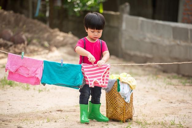 Spaß glückliches baby, zum der kleidung zu waschen und zu lachen und an einem sonnigen sommer.